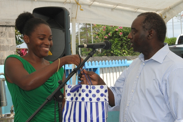Ms. Anastasha Elliott, one of 18 participants at the Essential Oils Workshop hosted by the Small Enterprise Development Unit in the Ministry of Finance on Nevis, presents Mr. Timothy Prescott, facilitator with a token of appreciation on behalf of the participants at the closing ceremony on May 23, 2018