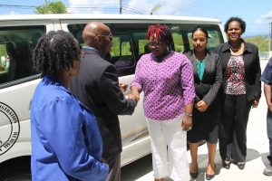 Mr. Timothy Caines, Member of the St. Christopher and Nevis Social Security Board hands over the keys to a new bus donated to the Ministry of Health by the Board to Hon. Hazel Brandy Williams on May 18, 2018 at the Social Security Building in Nevis. Fellow Board Member Mrs. Mrs. Jacqueline Brooks-Jeffers looks on
