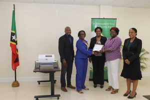 (l-r) Mr. Timothy Caines and Mrs. Jacqueline Brooks-Jeffers, Members of the St. Christopher and Nevis Social Security Board hand over an EKG machine, a gift from the Board, to Hon. Hazel Brandy Williams, Minister of Health; Dr. Judy Nisbett, (centre); and Mrs. Nicole Slack-Liburd, Permanent Secretary in the Ministry of Health on May 18, 2018 at the Social Security Building in Nevis