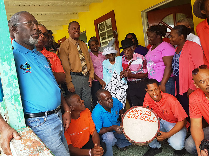 (l-r top row) Mr. Abonaty Liburd, Executive Director of the Culturama Secretariat. Mr. Jerome Rawlins, Chief Executive Officer of the Nevis Cultural Development Foundation, Hon. Eric Evelyn Minister of Culture and other staff of the Nevis Cultural Development Foundation visiting Cultural icon Mr. David Freeman (fourth from right) on his 90th birthday on February 16, 2018, at his home in Gingerland with Mrs. Clarestine Freeman (fifth from right), his wife standing beside him