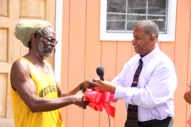 Hon. Eric Evelyn, Minister responsible for Social Development on Nevis presents the keys to a new home at Spring Hill to Joseph Belgrave at a handing over ceremony on June 14, 2018