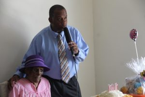 Hon. Eric Evelyn, Minister responsible for the Ministry of Community Development delivering congratulatory remarks to Ms. Ilene Smithen on the occasion of her 101stbirthday on June 20, 2018