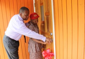 With a little help from Hon. Eric Evelyn, Minister responsible for Social Development on Nevis, new home owner Ms. Lorraine Cassandra Phillip opens the front door to her dwelling home at Fountain Village a gift from the ministry on June 14, 2018