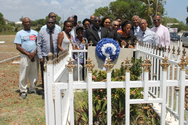 Hon. Alexis Jeffers (5th from left, first row) colleague ministers in the Nevis Island Administration and well-wishers at the grave-site of the late Malcolm Guishard to mark the 11th anniversary of his passing on June 11, 2018 at Bath Cemetery. First Lady Mrs. Sharon Brantley stands on his immediate right and Ms. Shenelle Guishard, daughter of the late Mr. Guishard stands on her immediate right