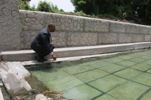 Hon. Mark Brantley, Premier of Nevis and Minister of Tourism takes a closer look at one of the pristine pools decked with new slabs at the Bath Stream in Bath Village on June 25, 2018