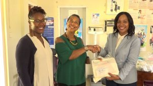 Dr. Jeanita Richardson, Professor at the University of Virginia hands over medical supplies to Mrs. Nicole Slack-Liburd, Permanent Secretary in the Ministry of Health while Dr. Kelsie Kelly looks on at the Charlestown Health Centre on June 19, 2018