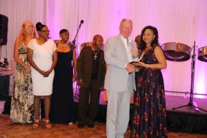 Mr. Tim Thuell, General Manager of the Nisbet Plantation Beach Club at Newcastle in Nevis, with some members of his staff accepting the Ministry of Tourism's Hotel of the Year Award from Mrs. Sharon Brantley, wife of Minister of Tourism Hon. Mark Brantley at the ministry's annual Tourism Awards Gala and Dance at the Four Seasons Resort on May 27, 2017