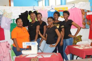 Ms. Mavis Parris (left) Clothing and Textiles teacher at the Charlestown Secondary School with some of her students at an exhibition (file photo)