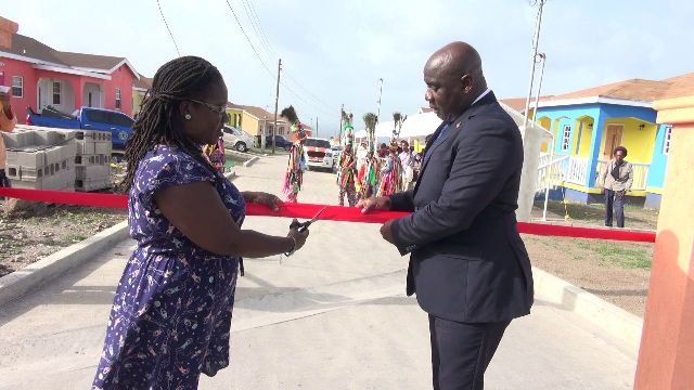 Mrs. Tracy Frazer, a homeowner at Cedar View Housing Development at Maddens, cuts the ribbon with Hon. Alexis Jeffers, Minister responsible for Housing and Lands, and Chairman of the Nevis Housing and Land Development Corporation Board of Directors at the official opening on September 20, 2018