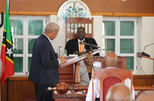 Hon. Spencer Brand, Minister of Physical Planning and Environment addressing a sitting of the Nevis Island Assembly at Hamilton House with Ms. Myra Williams, Clerk of the Assembly and Hon. Farrel Smithen, President of the Assembly looking on (file photo)