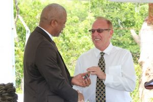 Hon. Spencer Brand, Minister of Water Services on Nevis receives keys for the pump station and wells at Maddens Estate from Mr. Michael Miville, Chief Executive Officer of Bedrock Exploration and Development Technologies LLC at a handing over ceremony on October 05, 2018
