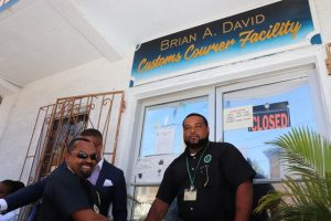 Hon. Mark Brantley, Premier of Nevis, and Mr. Sheldon David, the son of the late Brian Anthony David being congratulated by Mr. Cynric Carey, Deputy Comptroller of the Customs and Excise Department on Nevis moments after the ribbon cutting and unveiling of the new name of the Customs Courier Facility in Charlestown on October 25, 2018