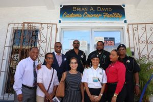 Photo caption: (L-r back row) Hon. Mark Brantley, Premier of Nevis; Mr. Cynric Carey, Deputy Comptroller of the Customs and Excise Department on Nevis; Mr. Sheldon David, son of the late Mr. Brian Anthony David; Mr. Kennedy DeSilva, Acting Comptroller of the St. Kitts and Nevis Customs and Excise Department. (Front row) Family members: Hon. Eric Evelyn; Ms Sheila Evelyn; Mrs. Joyce Powell-Broadbelt; Mrs. Kaymoye Carey and Ms. Shanelle David share a light moment after the renaming ceremony of the Customs Courier Facility in Charlestown on October 25, 2018