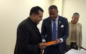 Hon. Mark Brantley, Premier of Nevis, exchanges copies of the signed agreement with Mr. Vishal Khann, President and Chief Executive Officer of Northern Pointe Development Ltd. on December 05, 2018, moments after they were signed, paving the way for the construction of a proposed Wyndham Grand resort at Long Haul Bay at Potworks on Nevis. Mrs. Hélène Anne Lewis, Legal Advisor in the Nevis Island Administration looks on