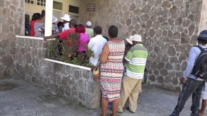 Persons lined up at the Nevis Island Administration building in Charlestown to receive their first $500 cheque from the Federal government's Poverty Alleviation Programme on December 24, 2018