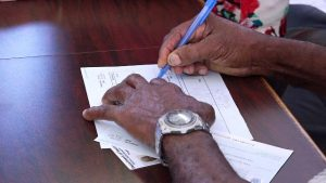 A beneficiary of the Federal government's Poverty Alleviation Programme signs for his first $500 monthly benefit cheque at the Nevis Island Administration building in Charlestown on December 24, 2018