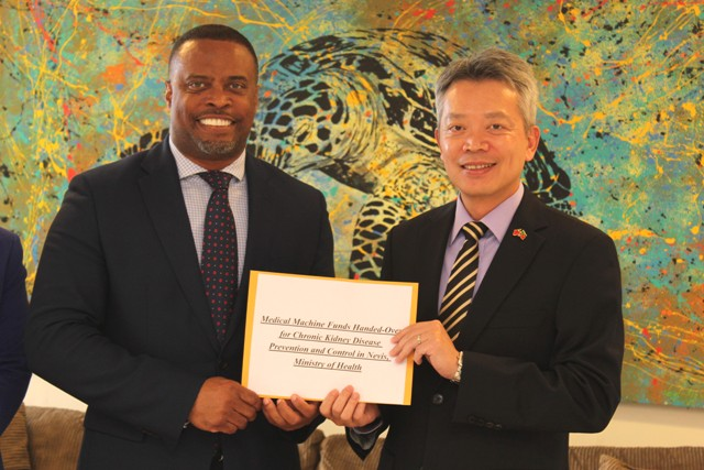 His Excellency Tom Lee, Resident Ambassador of the Republic of China (Taiwan) to St. Kitts and Nevis (right), hands over a cheque to Hon. Mark Brantley, Premier of Nevis and Minister of Health, at his Pinney's Estate office on December 04, 2018, for procuring two hemodialysis machines and their water-related systems