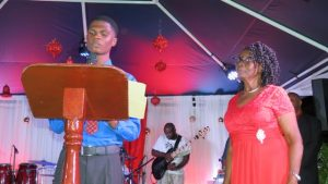 Mr. Recardoe Rodriquez, Youth Junior Minister of Tourism reads profile of Mrs. Zaiditor Olive Jeffers of Craddock Road, Patron of the annual Christmas Tree Lighting Ceremony in Charlestown on December 05, 2018
