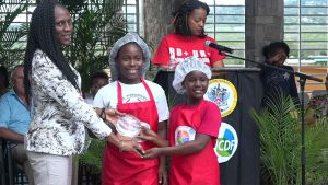 Mrs. Shelisa Martin-Clarke Acting Permanent Secretary in the Ministry of Health presents a trophy to joint 1st place winners in the MyHealthyPlate Junior Chef Competition, to Ms. La-Taivia Powell and Ms. Alicia Wallace of the St. James Primary School, at the Nevis Performing Arts Centre courtyard on April 15, 2019
