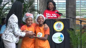 Mrs. Shelisa Martin-Clarke Acting Permanent Secretary in the Ministry of Health presents a trophy to joint 1st place winners in the MyHealthyPlate Junior Chef Competition, to Ms. Lanaiva Jones and Ms. Di Tricia France of the Charlestown Primary School, at the Nevis Performing Arts Centre courtyard on April 15, 2019