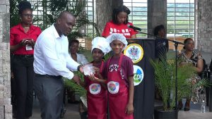 Mr. Randy Elliott, Director of Agriculture presents joint 3rd place winners in the MyHealthyPlate Junior Chef Competition, to Mr. Aaron Woolward and Ms. J' rell Powell  of the Ivor Walters Primary School, at the Nevis Performing Arts Centre courtyard on April 15, 2019