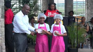 Mr. Randy Elliott, Director of Agriculture presents a trophy to joint 3rd place winners in the MyHealthyPlate Junior Chef Competition, to Mr. Yadav Pratyaksh and Ms. Khayla Claxton of the Nevis Academy, at the Nevis Performing Arts Centre courtyard on April 15, 2019