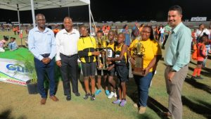 Athletes and staff of the Elizabeth Pemberton Primary School winners in Zone B of the 27th annual Gulf Insurance Inter-Primary Schools Championship with their trophy presented by (extreme right) Mr. Henry Francis Human Resource Manager of the Gulf Insurance Ltd. in Trinidad at the Nevis Athletic Stadium at Low Ground on April 03, 2019. Also present are (second from right) Hon. Eric Evelyn, Minister of Youth and Sports on Nevis, (second from left) Principal Ms. Shenelle Pemberton and (extreme left) another Gulf Insurance Representative