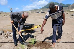 Hon. Spencer Brand, Minister responsible for the Environment, plants a Sea Grape tree at the Nevis Historical Conservation Society's New River Coconut Walk Restoration Project on April 23, 2019 with assistance from Mr. Keithley Amory, Project Coordinator