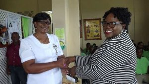 (L-r) Averil Walters, Community Health Nurse at the Gingerland Health Centre, one of 116 nurses receiving a token of appreciation from Hon. Hazel Brandy-Williams, Junior Minister of Health on Nevis, on May 13, 2019