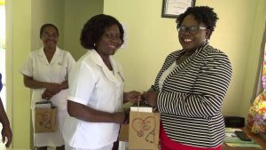 (L-r) Dahlia Simmonds, Community Health Nurse at the Brown Hill Health Centre, one of 116 nurses receiving a token of appreciation from Hon. Hazel Brandy-Williams, Junior Minister of Health on Nevis, on May 13, 2019, while Nurse Donna Hill, Community Health Nurse in charge of the centre looks on with her gift in hand