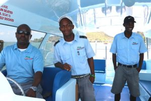 "(L-r) Water Taxi Operator on Nevis Capt. Wincent Perkins of Islander Watersports accompanied by Mr. Raymundo Nisbett, First Mate; and Mr. Verez Dore, Second Mate on board ""Point Setter"" a 14 seater boat in the company's fleet of seven"