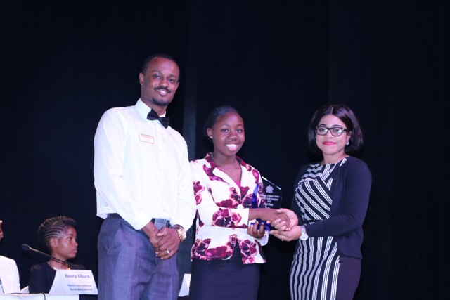Ms. Brianne Chapman the new Youth Junior Minister of Tourism on Nevis receiving her winning trophy at The Bank of Nevis Ltd. Tourism Youth Congress on May 21, 2019, from Ms. Oksana Williams, Tourism Youth Congress Coordinator in the Ministry of Tourism while Mr. Phéon Jones, the bank's Marketing Officer