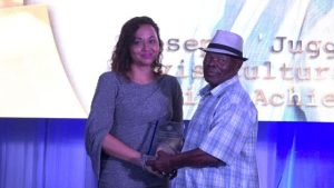 "Mr. Joseph ""Juggo"" Brandy receives the award for Nevis Cultural Tourism Lifetime Achievement Award from First Lady Mrs. Sharon Brantley at the Ministry of Tourism' s Nevis Tourism Industry Awards ceremony on May 25, 2019, on the grounds of Government House at Bath Plain"