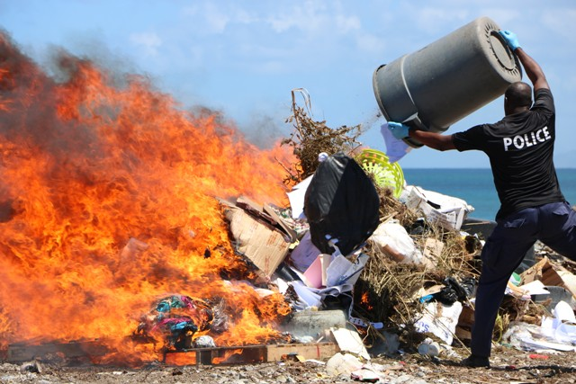 Inspector James Stephen, Head of the Nevis Task Force based at the Charlestown Police Station, feeds the fire burning more than EC$1million worth of illegal drugs in an operation at the Nevis Solid Waste Management Authority landfill at Long Point on June 13, 2019