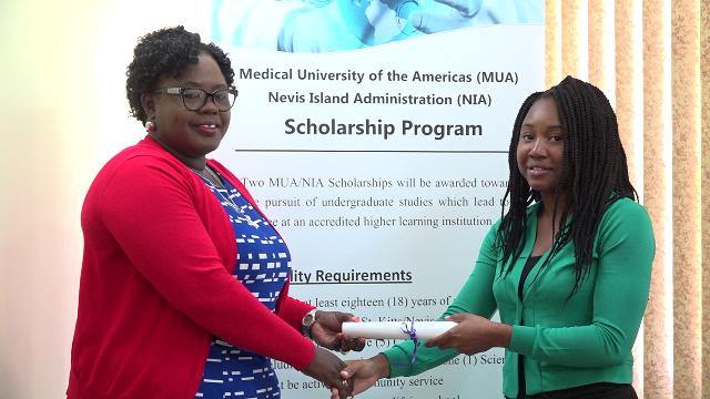 Hon. Hazel Brandy-Williams presents MUA/NIA Scholarship award to Ms. Dericia Bryant at the Ministry of Finance Conference Room in Charlestown on July 17, 2019, to pursue a Bachelor of Science in Interdisciplinary Studies with a focus on Special Education