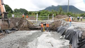 Workers from contractors Surrey Paving and Aggregate Co. Caribbean Ltd. laying the foundation for the installation of a box culvert to alleviate flooding in the Cades Bay area on July 29, 2019