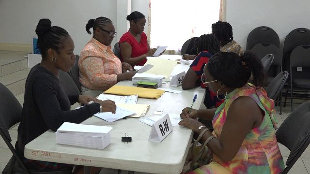 Some of the 361 Four Seasons Resort, Nevis workers affected by a temporary closure receiving assistance cheques from the Nevis Island Administration through staff of the Treasury Department at the St. Paul's Anglican Church Hall in Charlestown on August 21, 2019