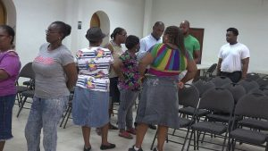 Mr. Colin Dore, Permanent Secretary in the Ministry of Finance in the Nevis Island Administration, assisting Four Seasons Resort, Nevis workers affected by a temporary closure at the St. Paul's Anglican Church Hall in Charlestown for smooth disbursement of assistance cheques from the Nevis Island Administration on August 21, 2019