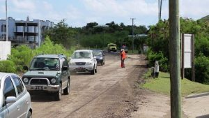 A flag lady operating near a corner of the road in Phase 1 of the Nevis Island Administration's EC$6.7 million Island Main Road Rehabilitation and Safety Improvement Project from Cotton Ground to Cliff Dwellers