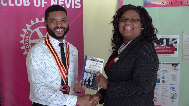 Mr. Kris Liburd, sitting President of the Rotaract Club of Nevis, presenting a gift of books to Ms. Zahnela Claxton, Principal Education Officer, on September 10, 2019 at the Department of Education