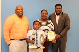 Mr. Ron Daniel and Mrs. Tresia Daniel and their son Rondre Daniel, winner in of the local leg of the 10th Annual OECS Courts Reading Competition; with Hon. Troy Liburd, Junior Minister of Education; at his office on November 18, 2019