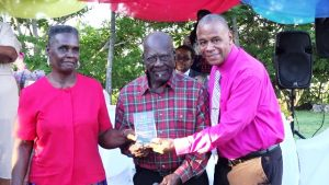"Hon. Eric Evelyn, Minister of Social Development presents gift to James and Edith Phillip on behalf of the Department Department of Social Services, Senior Citizens Division, of for their contribution to the development of Nevis at an event dubbed ""Afternoon of the lawn"" on the grounds of Government house at Bath Plain on October 31, 2019"
