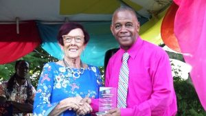 "Thelma ""TC"" Claxton receives her token of appreciation from Hon. Eric Evelyn, Minister of Social Development on behalf of the Department Department of Social Services, Senior Citizens Division, of for their contribution to the development of Nevis at an event dubbed ""Afternoon of the lawn"" on the grounds of Government house at Bath Plain on October 31, 2019"