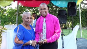 "Uretha Flanders receives her token of appreciation from Hon. Eric Evelyn, Minister of Social Development on behalf of the Department Department of Social Services, Senior Citizens Division, of for their contribution to the development of Nevis at an event dubbed ""Afternoon of the lawn"" on the grounds of Government house at Bath Plain on October 31, 2019"