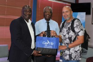 A representative from Cape Air presents a gift bag to Hon. Alexis Jeffers, Deputy Premier of Nevis (left) and Mr. Oral Brandy, General Manager of the Nevis Air and Sea Ports Authority (middle) at the Vance W. Amory International Airport VIP lounge on December 12, 2019, in celebration of the airline's return to Nevis