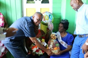 "Hon. Eric Evelyn, Minister responsible for seniors on Nevis presents a gift basket in collaboration with City Drug Store as a token of appreciation to Ms. Eliza ""Liza Liburd Jeffers"" Flanders in celebration of her 100th birthday at her home in Hamilton on November 30, 2019, while her son Mr. Elton Liburd (right) looks on"