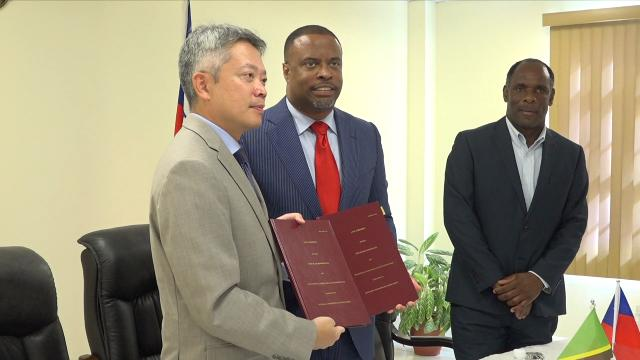 (L-r) His Excellency Tom Lee, Republic of China (Taiwan)'s Resident Ambassador to St. Kitts and Nevis, and Hon. Mark Brantley, Premier of Nevis, showing off copies of the agreement for the Loan Agreement between the Nevis Island Administration and Taiwan International Cooperation and Development Fund in relation to Nevis Small Enterprise Re-lending Project, moments after signing the agreement at Government Headquarters at Pinney's Estate on December 30, 2019. Mr. Colin Dore, Permanent Secretary in the Ministry of Finance looks on
