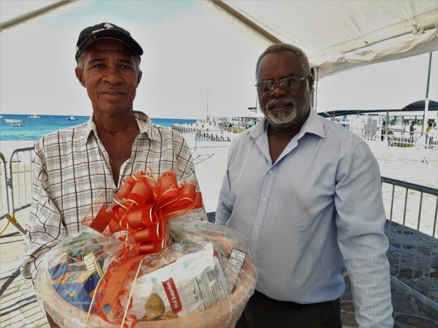 (L-r) Mr. Anthony Cranston, a sanitation worker at the Ministry of Health on Nevis being presented with a fruit basket by Mr. Ken Pembertion Manager of the Charlestown Port as a token of appreciation from the Nevis Air and Sea Ports Authority on Tuesday December 24th, 2019 at the Charlestown Pier