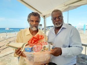 (L-r) Mr. Donald Browne, one of the sanitation workers at the Ministry of Health on Nevis being presented with a fruit basket by Mr. Ken Pembertion Manager of the Charlestown Port as a token of appreciation from the Nevis Air and Sea Ports Authority on Tuesday December 24th, 2019 at the Charlestown Pier