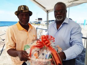 (L-r) Mr. Patrick Smithen, one of the sanitation workers at the Ministry of Health on Nevis being presented with a fruit basket by Mr. Ken Pembertion Manager of the Charlestown Port as a token of appreciation from the Nevis Air and Sea Ports Authority on Tuesday December 24th, 2019 at the Charlestown Pier